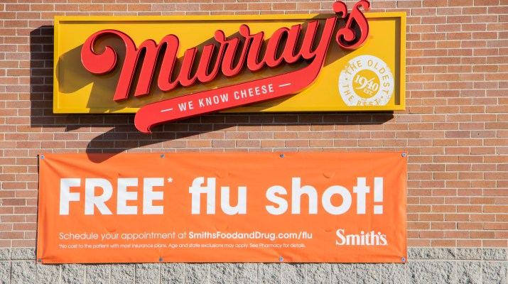 "A sign that says ""Free Flu Shot"" is on a white building under a red and orange ""Murrays"" sign."