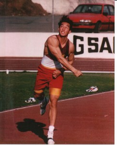 A man in a red track and field uniform releases a throw.