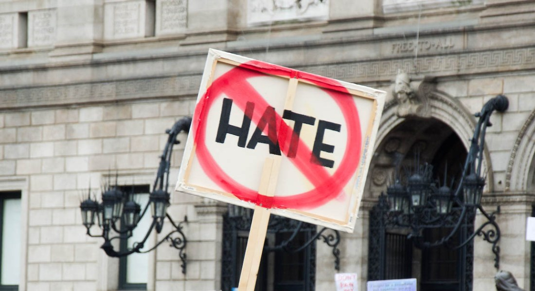 "A square sign has the word ""HATE"" crossed out in red."