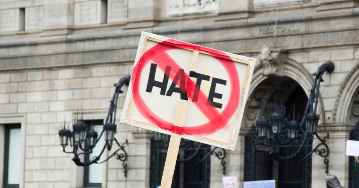 """A square sign has the word """"HATE"""" crossed out in red."""