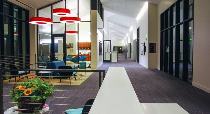 an academic building's hallway with glass windows and circular lights