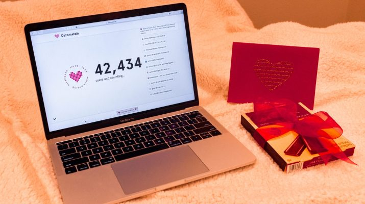 A computer with the data match website open sits next to a box of chocolates on a pink blanket.