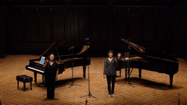 Two female music professors stand on stage in front of two pianos.