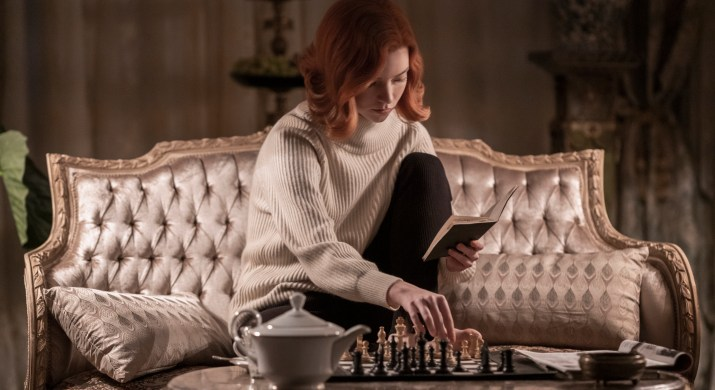 A red-haired woman sits on a couch playing piano.