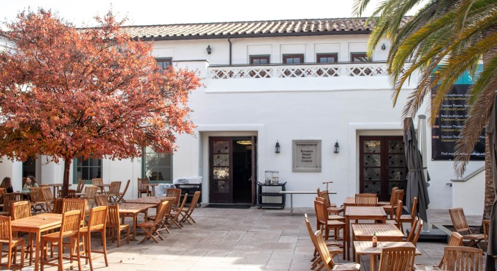 A white building sits behind a white tile patio filled with wooden tables surrounded by orange trees.