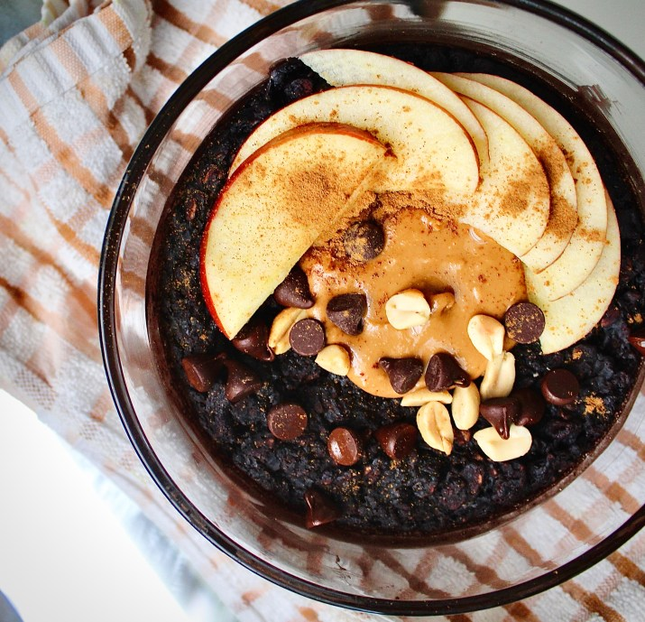 A bowl of baked oats decorated with chocolate chips and peanut butter with apple slices on the side