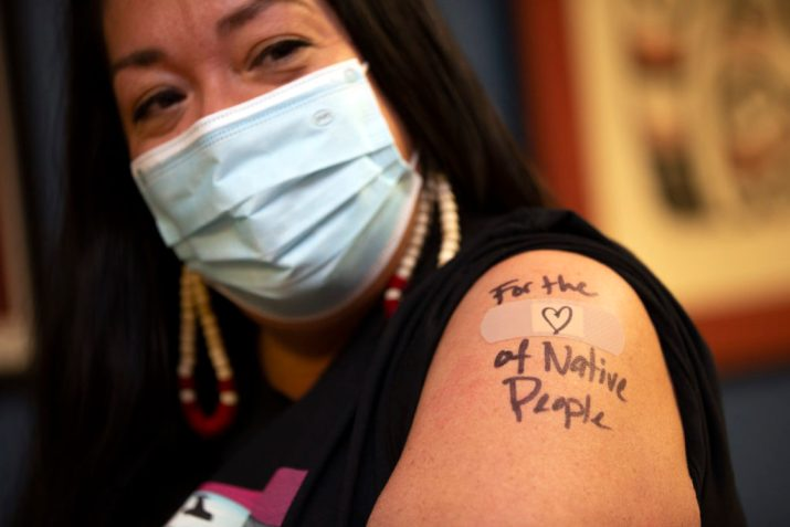 """An Indigenous American woman receives a shot of the COVID-19 vaccine. Written in pen on her arm are the words """"For the love of Native People."""""""