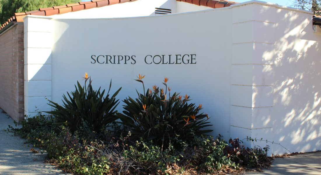 A white wall with Scripps College written on it with some plants underneath.