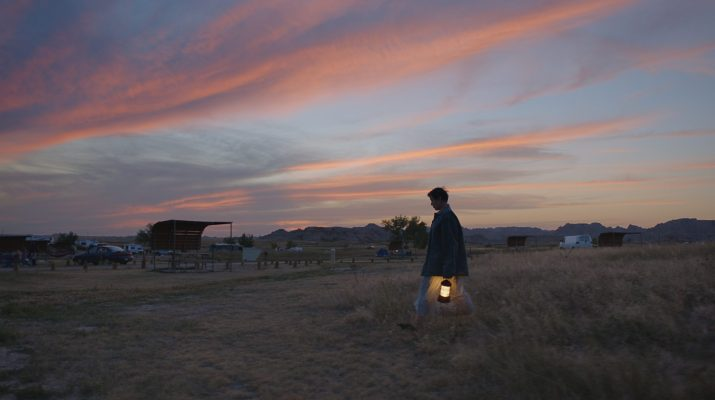 A woman holding a lantern strides across a field at sunset.