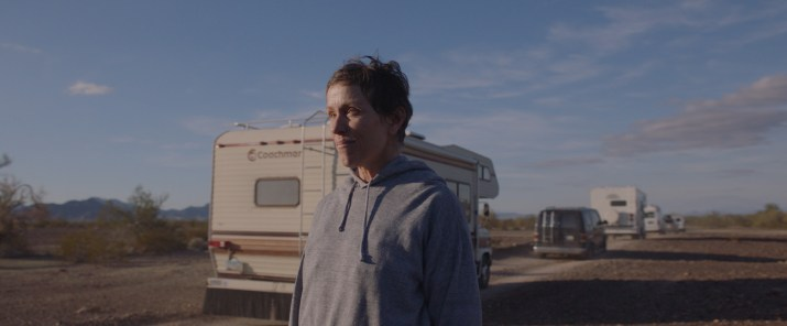 A woman wearing a gray sweatshirt with short hair stands next to a road looking at a trailer driving away.