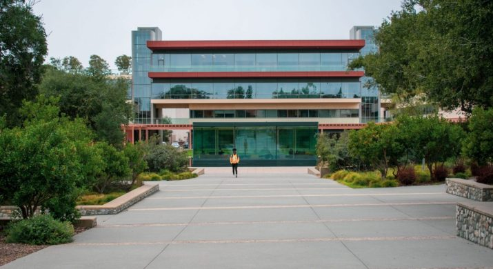A Claremont McKenna College building stands in the background of a grey asphalt path.
