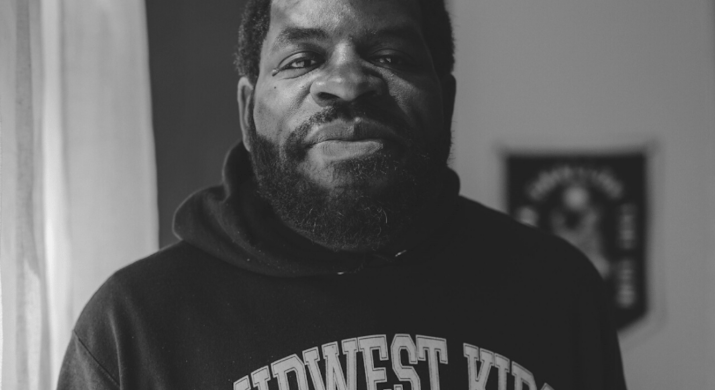 """A man wearing a """"Midwest Kids"""" hoodie looks at the camera."""