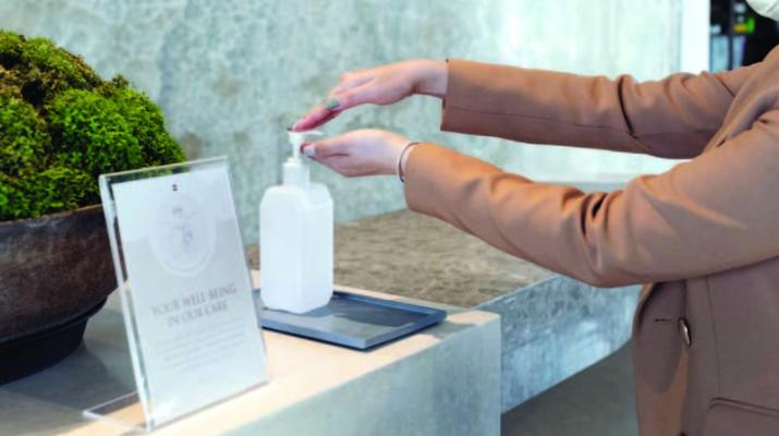 A person reaches out to pump some hand sanitizer into their hands.