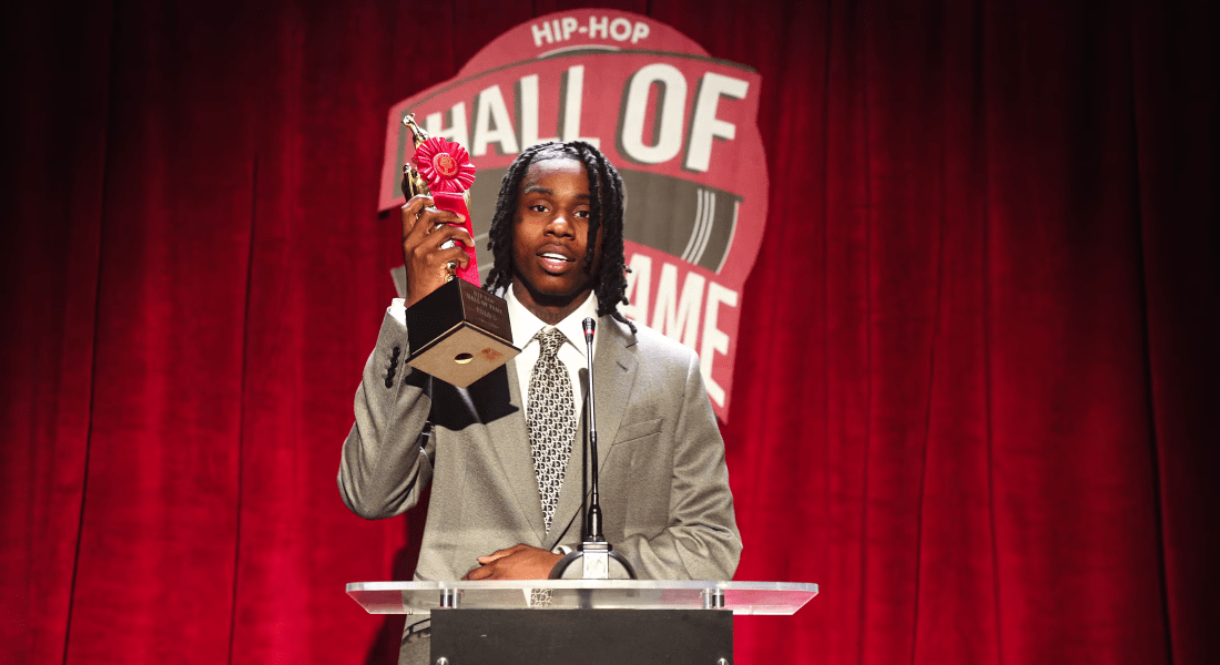 "Polo G in his Rapstar music video wears a grey suit and holds up a trophy that reads ""Hip Hop Hall of Fame Polo G."""