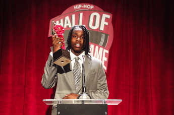 """Polo G in his Rapstar music video wears a grey suit and holds up a trophy that reads """"Hip Hop Hall of Fame Polo G."""""""