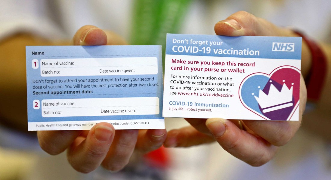 Two blue and white cards that outline the days and time of COVID-19 vaccines are held next to each other.