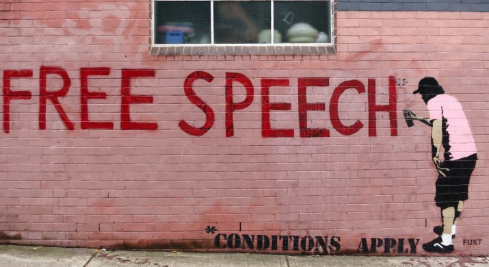 """A red brick wall has a grafitti picture of a person spray painting """"FREE SPEECH *conditions apply""""."""