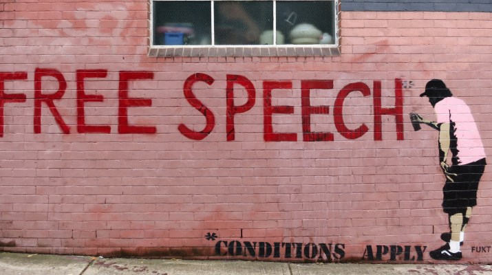 "A red brick wall has a grafitti picture of a person spray painting ""FREE SPEECH *conditions apply""."