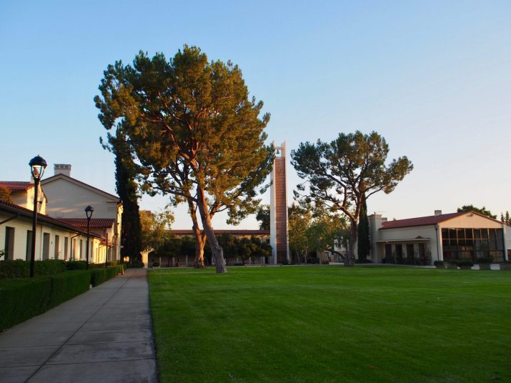 Cream-colored buildings with red tiled roofs are surrounded by grass lawns and trees.