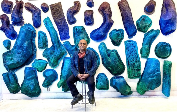 A college professor sits in front of a wall displaying large teal, blue and purple aluminum tree trunk molds.