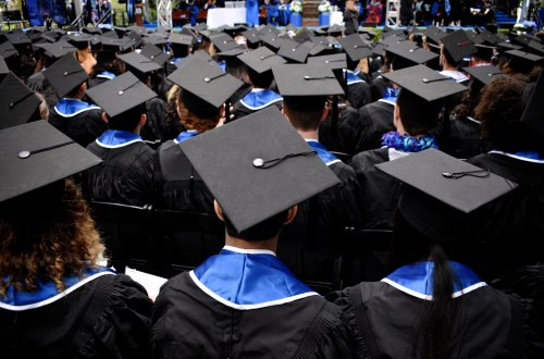 Students gathered for graduation wearing black caps and blue sashes.