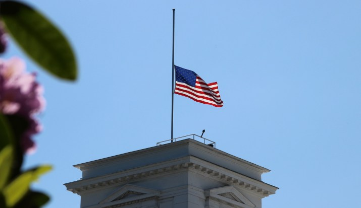An American flag at half mast waves in the wind.