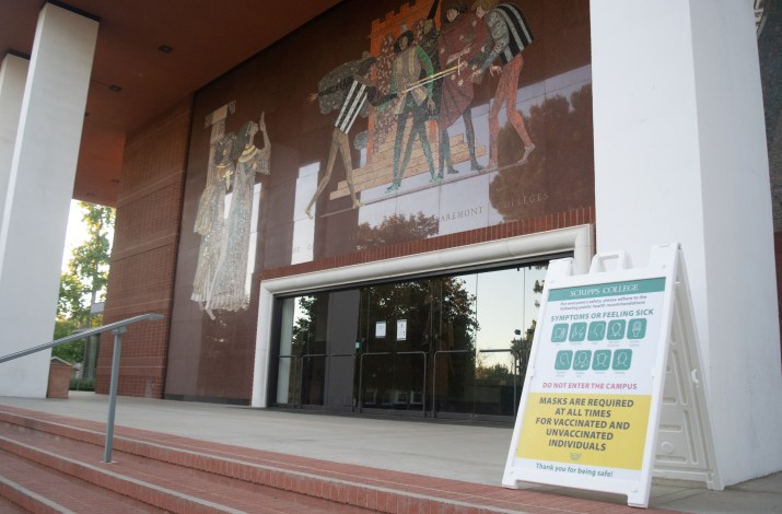 A green sign with information regarding COVID policies is placed inf front of a large theater with closed doors.