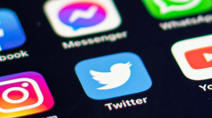 A black smartphone screen shows a list of social networking applications including Twitter.