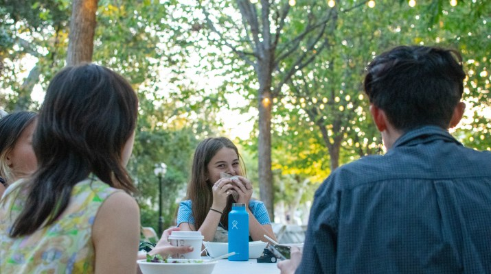 A girl, wiping her mouth, smiles at the camera as she finishes a meal with friends.