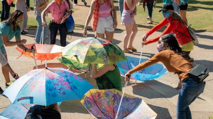 A group of people twirl colorful umbrellas on the ground and a few crouch, holding umbrellas.