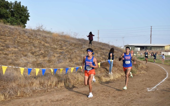 Two members of the Pomona-Pitzer cross country team compete on a dirt track.