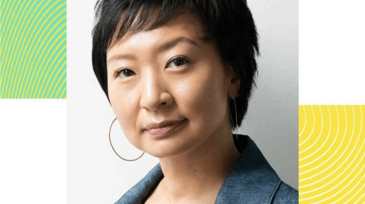 A headshot of an Asian woman with short black hair, wearing a blue shirt and hoop earrings.