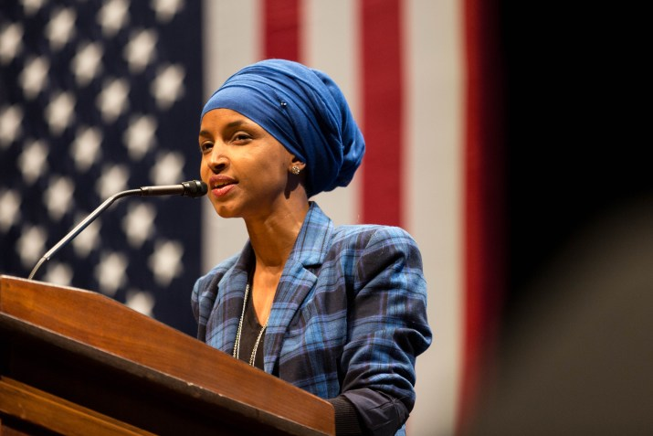 A female politician gives a speech with an American flag in the background.