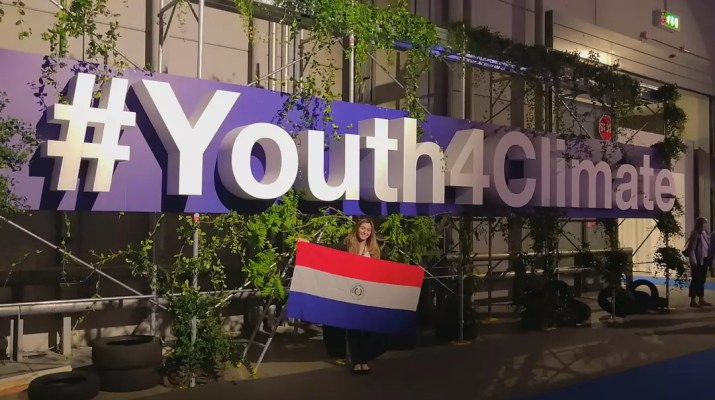 Diana Vicezar PZ '24 stands in front of a sign saying #Youth4Climate with the flag of Paraguay in her hands