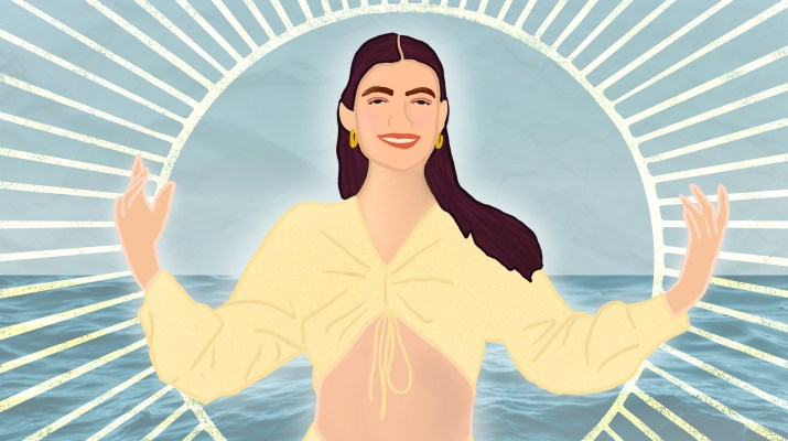 Lorde stands in front of the ocean, her arms spread out.