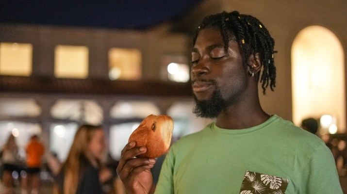 A student prepares to eat Challah on its opening night.