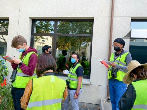 Students in yellow vests observe birds and take notes.