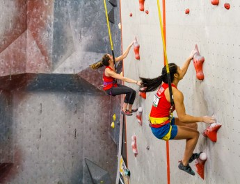 Two sports climbers climb side by side.