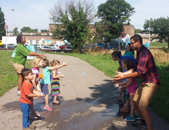 Children and adults toss water balloons in Tacony Creek Park