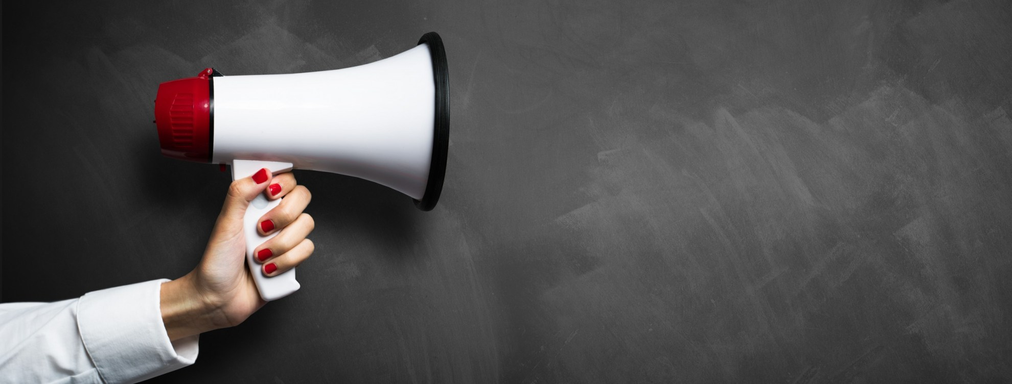 Woman's hand holding a red & white megaphone against a chalkboard backdrop.