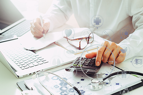 Health economics expert conducting a clinical-economic study using a laptop and calculator.