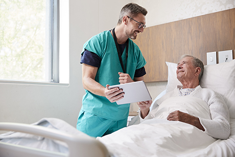 Surgeon next to a patient, explaining the new medical device.