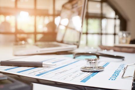 Stethoscope sitting on medical insurance reimbursement documents.