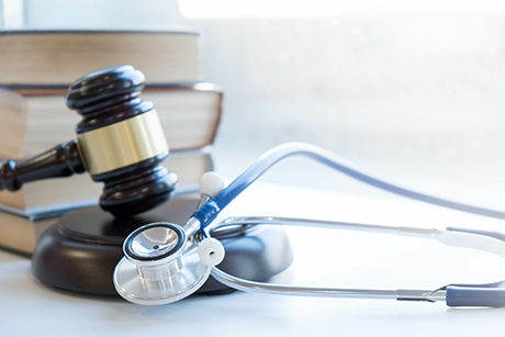 Gavel & stethoscope in front of medical and law books.
