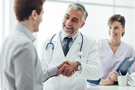 Smiling doctor shaking hands with provider educator.