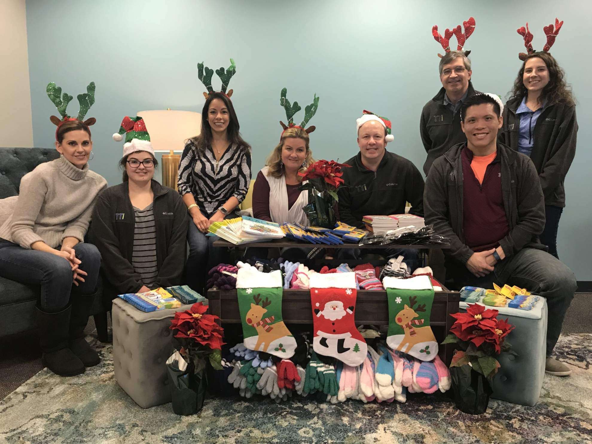 TTi's team smiling with a collection of gifts collected for NESAP including Christmas stockings, mittens, books, and other items. The team are wearing Christmas hats & reindeer antlers.