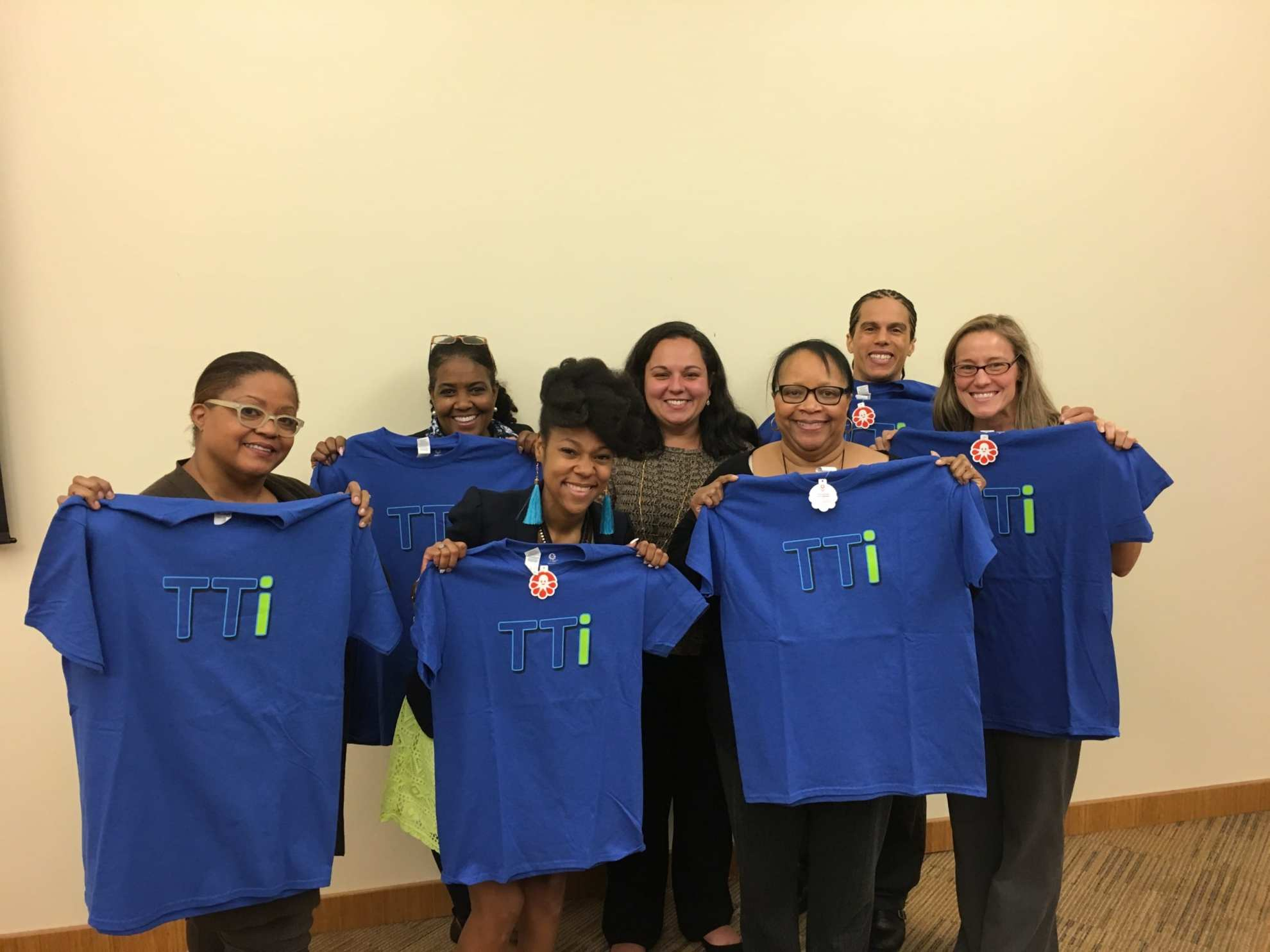Group of TTi employees smiling holding up blue TTi T-Shirts