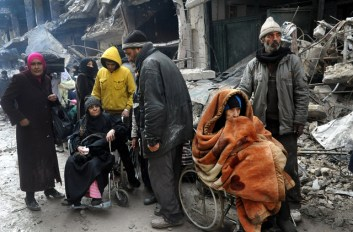FILE - In this Feb. 4, 2014, file photo released by the Syrian official news agency SANA, Palestinian residents of the besieged refugee camp of Yarmouk wait at the gate of the camp to receive aid supplies from the United Nations on the southern edge of the Syrian capital, Damascus. The deteriorating situation brought on by Syria's civil war prompted the U.N. Security Council to call an emergency meeting Monday, April 6, 2015, to discuss Yarmouk, calling for safe evacuation for the Palestinians, protection for the refugees, and humanitarian access to the camp. (AP Photo/SANA, File)
