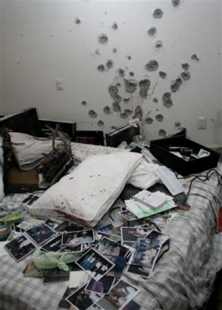 A wall with bullet holes is seen next to photos and other things sitting on a bed in an apartment in Cuernavaca, Mexico, Thursday, Dec. 17, 2009. A Mexican navy official said that alleged drug cartel chief Arturo Beltran Leyva and three members of his cartel were slain Wednesday inside the apartment during a shootout with sailors. (AP Photo/Antonio Sierra)