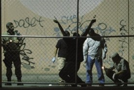 Police and army soldiers inspect the site where a dead man hangs from his wrists handcuffed to a fence in a night club parking lot in the border city of Ciudad Juarez, Mexico, late Monday, Aug. 31, 2009. The body was found in the same place where eight others were executed a few weeks ago. (AP Photo)